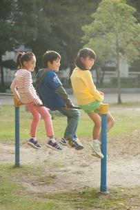 公園で鉄棒に腰かける子供男女3人の写真素材 [FYI01529481]
