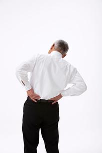 腰痛で腰に手をやる中高年男性の写真素材 [FYI01529565]