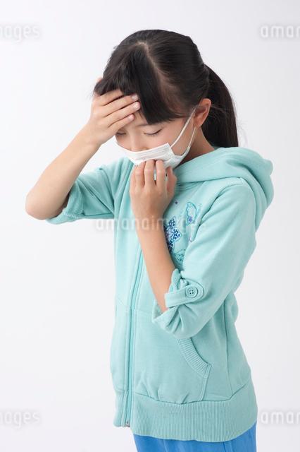 マスクと額に手をやる女の子の写真素材 [FYI01529575]