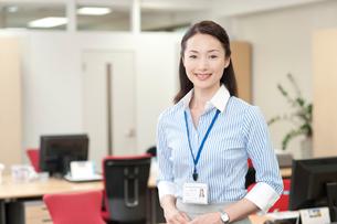 オフィスの中で立つIDカードを首にかけたOLの写真素材 [FYI01529621]