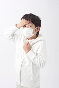 マスクをして額に手をやる男の子の写真素材 [FYI01529703]