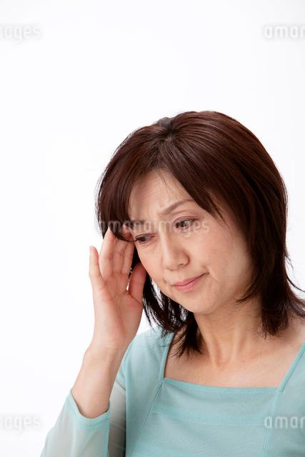頭痛で頭に手をやる中高年女性の写真素材 [FYI01529711]