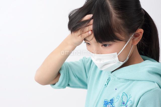 マスクをして額に手をやる女の子の写真素材 [FYI01529714]