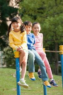 公園で鉄棒に腰かける子供男女3人の写真素材 [FYI01529717]