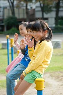 公園で鉄棒に腰かけて手を振る子供男女3人の写真素材 [FYI01529724]