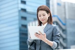 オフィス街に立ってタブレット型PCを持つ20代OLの写真素材 [FYI01529765]