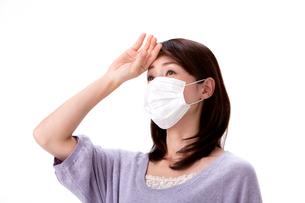 発熱で頭に手をやるマスクをした女性の写真素材 [FYI01529770]