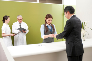 病院の受付で名刺交換するMRと女性事務員の写真素材 [FYI01529776]