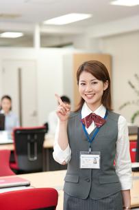 オフィスで人差指で指差しするIDカードを首にかけた20代OLの写真素材 [FYI01529790]