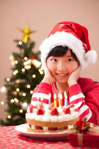 クリスマスでケーキとプレゼントを前に微笑む女の子の写真素材 [FYI01529799]