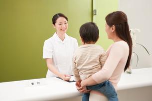 病院の受付で受診受付をする女性事務員と子供を抱いた女性の写真素材 [FYI01529809]