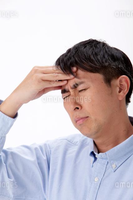 発熱で頭に手をやる男性の写真素材 [FYI01529826]