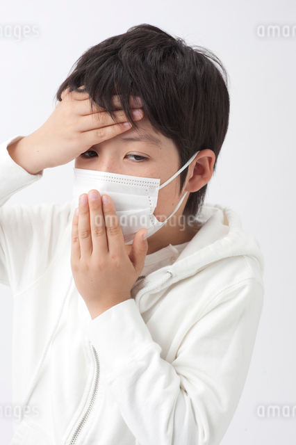 マスクと額に手をやる男の子の写真素材 [FYI01529832]