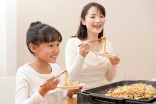 ホットプレートの焼そばを食べる母と女の子の写真素材 [FYI01529848]