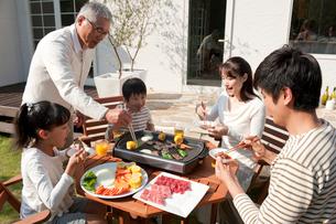 家の庭で焼肉を食べる3世代家族の写真素材 [FYI01529864]