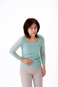 腹痛でお腹に手をやる中高年女性の写真素材 [FYI01529886]