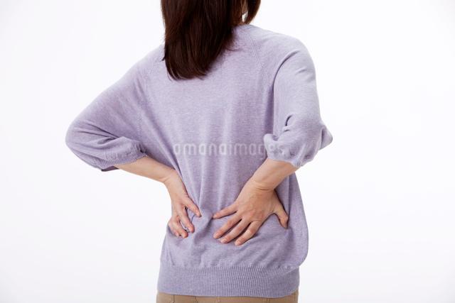 腰痛で腰に手をやる女性の後姿の写真素材 [FYI01529910]