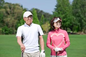 ゴルフコースを回る中高年男性と女性のカップルの写真素材 [FYI01529919]