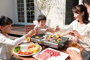 家の庭で焼肉を食べる4人家族の写真素材 [FYI01529946]