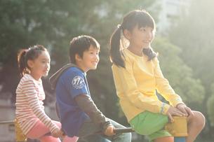 公園で鉄棒に腰かける子供男女3人の写真素材 [FYI01529958]