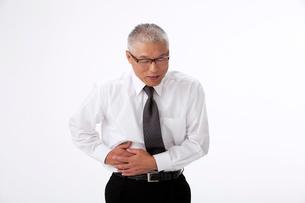 腹痛でお腹に手をやる中高年男性の写真素材 [FYI01529959]