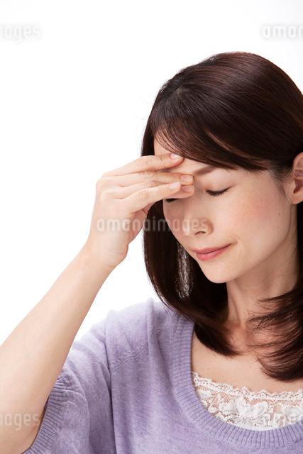 発熱で頭に手をやる女性の写真素材 [FYI01529962]