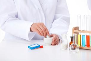 リトマス試験紙と乳鉢と乳棒で薬剤を混ぜる手の写真素材 [FYI01529974]