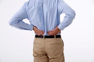 腰痛で腰に手をやる男性の写真素材 [FYI01529980]