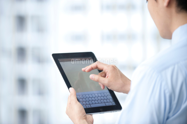 タブレットPCを使うビジネスマンの写真素材 [FYI01529987]