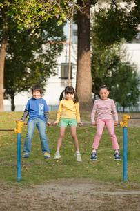 公園で鉄棒に腰かける子供男女3人の写真素材 [FYI01529992]