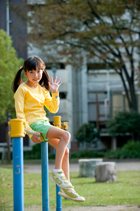 公園で鉄棒に腰かけ手を振る女の子の写真素材 [FYI01530009]
