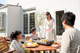 家の庭で焼肉をする4人家族の写真素材 [FYI01530029]