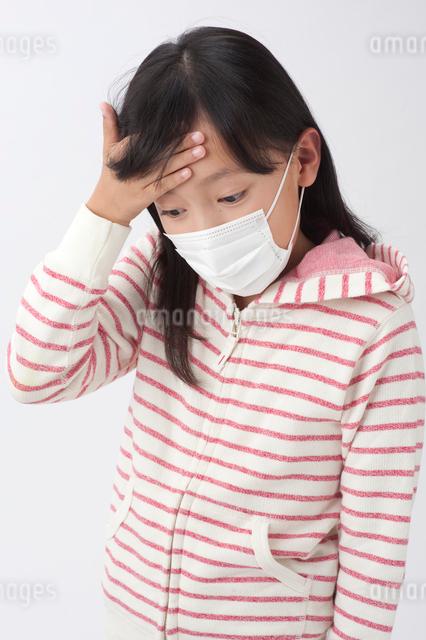 マスクと額に手をやる女の子の写真素材 [FYI01530037]