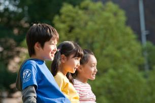 公園で鉄棒に腰かける子供男女3人の写真素材 [FYI01530050]