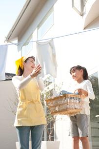洗濯物を干す女性と手伝う女の子の写真素材 [FYI01530057]