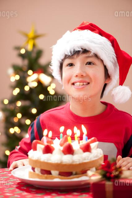 クリスマスでケーキとプレゼントを前に微笑む男の子の写真素材 [FYI01530108]