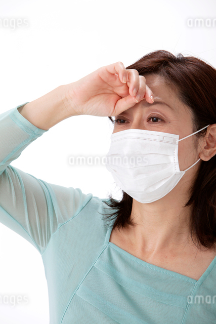 発熱で頭に手をやるマスクをした中高年女性の写真素材 [FYI01530165]