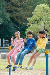公園で鉄棒に腰かけて手を振る子供男女3人の写真素材 [FYI01530183]