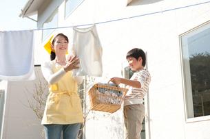 洗濯物を干す女性と手伝う男の子の写真素材 [FYI01530200]