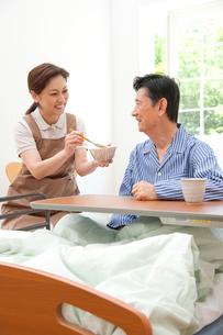 介護ベッドの老人に食事の世話をする介護ヘルパーの写真素材 [FYI01530204]
