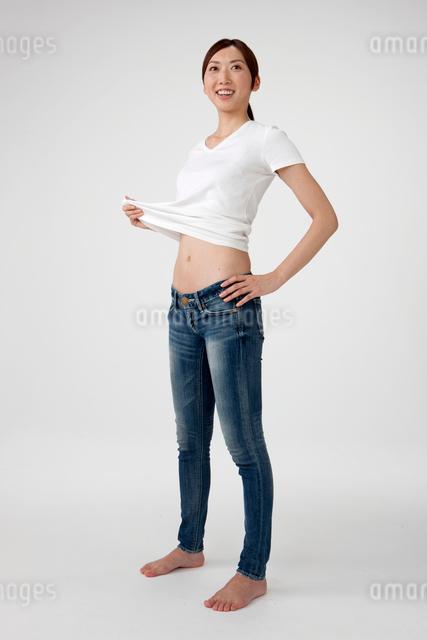 お腹を出したTシャツとジーンズを着た20代女性の写真素材 [FYI01530446]