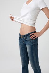 お腹を出したTシャツとジーンズを着た20代女性の写真素材 [FYI01530755]