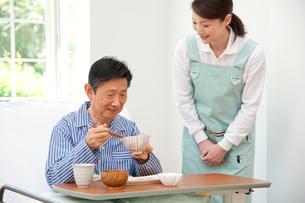 介護ベッドの老人に食事の世話をする介護ヘルパーの写真素材 [FYI01530932]