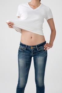 お腹を出したTシャツとジーンズを着た20代女性の写真素材 [FYI01530960]