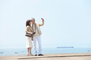 海のリゾートへ旅行中の中年夫婦の写真素材 [FYI01531026]