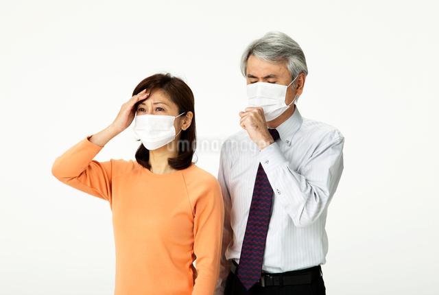 頭痛発熱と咳をしてマスクをする中年夫婦の写真素材 [FYI01531049]
