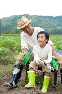 畑の中で一輪車に腰掛ける父と男の子の写真素材 [FYI01531075]