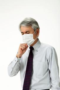 咳をしてマスクをする中年男性の写真素材 [FYI01531151]
