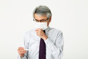 体温計を見て咳をしてマスクをする中年男性の写真素材 [FYI01531227]