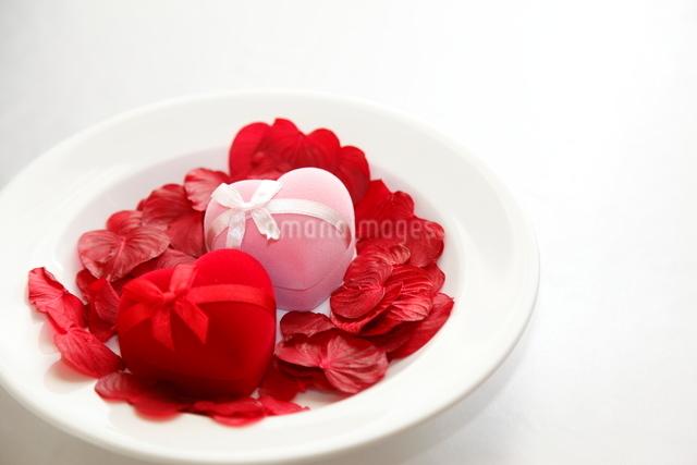 皿のピンクと赤のジュエリーボックスとバラの花びらの写真素材 [FYI01531286]